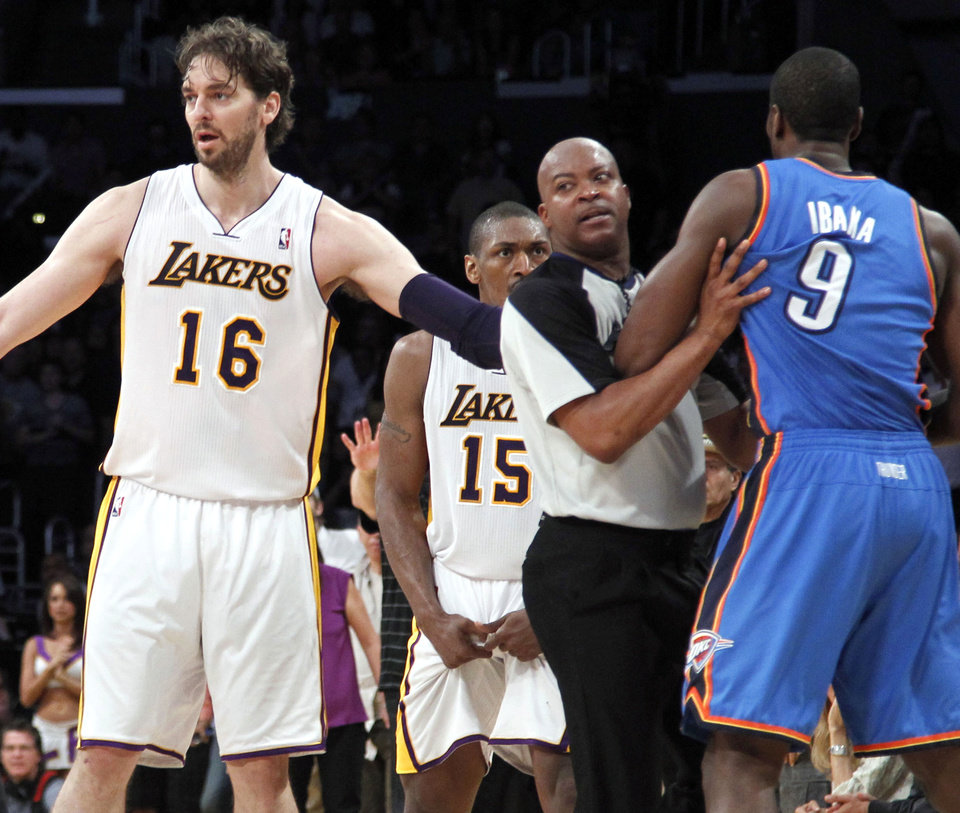 Los Angeles Lakers\' Pau Gasol (16), of Spain, stands between an official and Oklahoma City Thunder player after Lakers\' Metta World Peace (15) was called for a double flagrant foul and ejected from the game in the first half of an NBA basketball game, Sunday, April 22, 2012, in Los Angeles. (AP Photo/Reed Saxon) ORG XMIT: LAS201