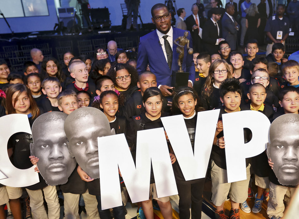 Photo - Kevin Durant poses for a photo with kids from the Oklahoma City Boys and Girls club during a news conference announcing Durant as the winner of the 2013-14 Kia NBA Basketball Most Value Player Award in Oklahoma City, Okla. on Tuesday, May 6, 2014. Photo by Chris Landsberger, The Oklahoman