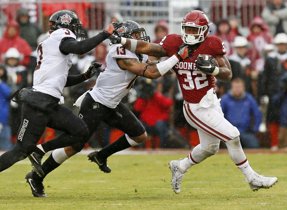 Photo - Oklahoma's Samaje Perine (32) runs the ball against Oklahoma State's Jordan Sterns (13) and Kenneth Edison-McGruder (3) during the Bedlam college football game between the Oklahoma Sooners (OU) and the Oklahoma State Cowboys (OSU) at Gaylord Family - Oklahoma Memorial Stadium in Norman, Okla., Saturday, Dec. 3, 2016. Photo by Nate Billings, The Oklahoman