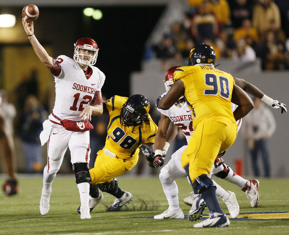 Photo - Oklahoma's Landry Jones (12) passes in the third quarter during a college football game between the University of Oklahoma and West Virginia University on Mountaineer Field at Milan Puskar Stadium in Morgantown, W. Va., Nov. 17, 2012. OU won, 50-49. Photo by Nate Billings, The Oklahoman