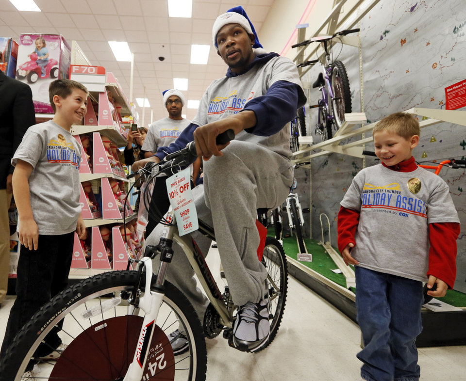 Photo - Kevin Durant of the Oklahoma City Thunder tries out a bicycle while shopping with Ryan Joy, 9, left, and Cadyn Joy, 6, during the Oklahoma City Thunder's annual Holiday Assist shopping spree at Target, 13924 N Pennsylvania, in Oklahoma City, Monday, Dec. 10, 2012. The ten families who participated in this year's shopping spree are from Sunbeam Family Services' Grandparents Raising Grandchildren program. Photo by Nate Billings, The Oklahoman