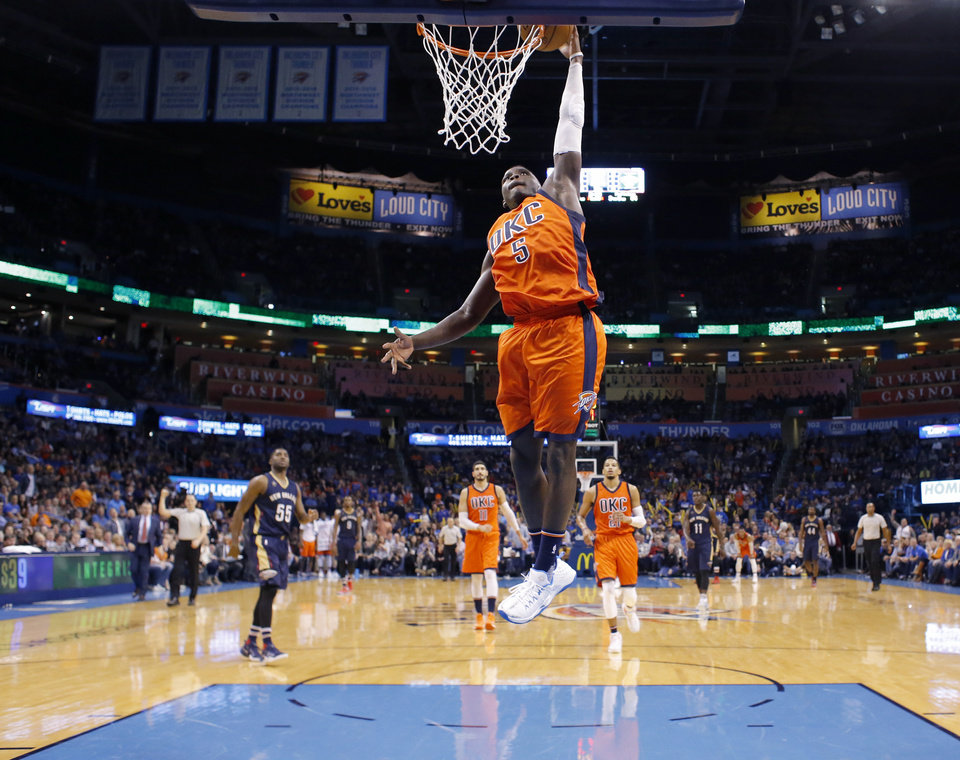 Photo - Oklahoma City's Victor Oladipo (5) dunks the ball during the NBA game between the Oklahoma City Thunder and the New Orleans Pelicans at the Chesapeake Energy Arena,  Sunday, Dec. 4, 2016. Photo by Sarah Phipps, The Oklahoman