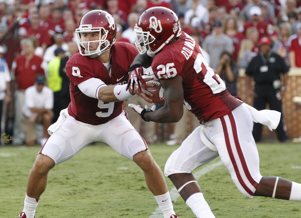 Oklahoma quarterback Trevor Knight (9) hands off to running back Damien Williams (26) in the first quarter of an NCAA college football game in Norman, Okla., Saturday, Aug. 31, 2013. (AP Photo/Sue Ogrocki)