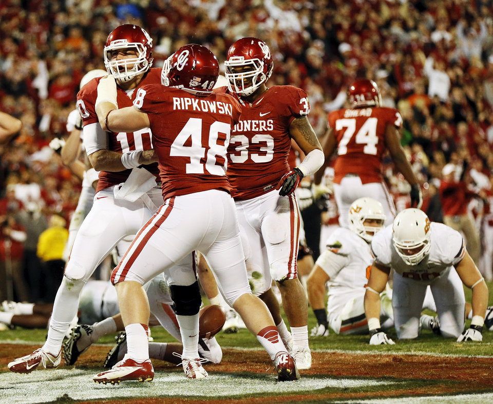 Photo - Oklahoma's Blake Bell (10) celebrates with Aaron Ripkowski (48) and Trey Millard (33) after rushing for a touchdown in the final minute of regulation during the Bedlam college football game between the University of Oklahoma Sooners (OU) and the Oklahoma State University Cowboys (OSU) at Gaylord Family-Oklahoma Memorial Stadium in Norman, Okla., Saturday, Nov. 24, 2012. The extra point on this touchdown tied the game. OU won, 51-48 in overtime. Photo by Nate Billings , The Oklahoman