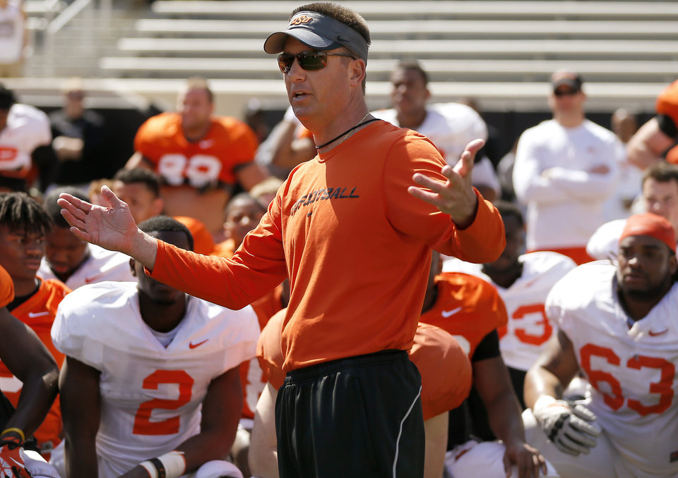 OSU coach Mike Gundy talks with his team after Oklahoma State's Orange Blitz football practice at Boone Pickens Stadium in Stillwater, Okla., Saturday, April 5, 2014.