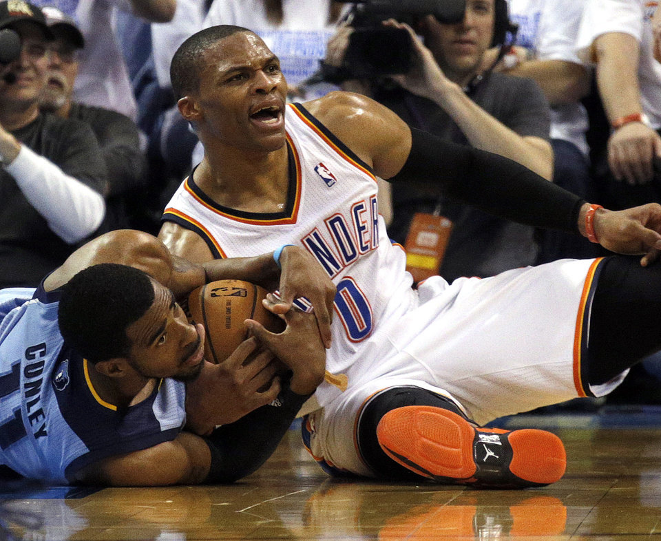 Photo - Oklahoma City's Russell Westbrook (0) and Memphis' Mike Conley (11) fight for a ball 