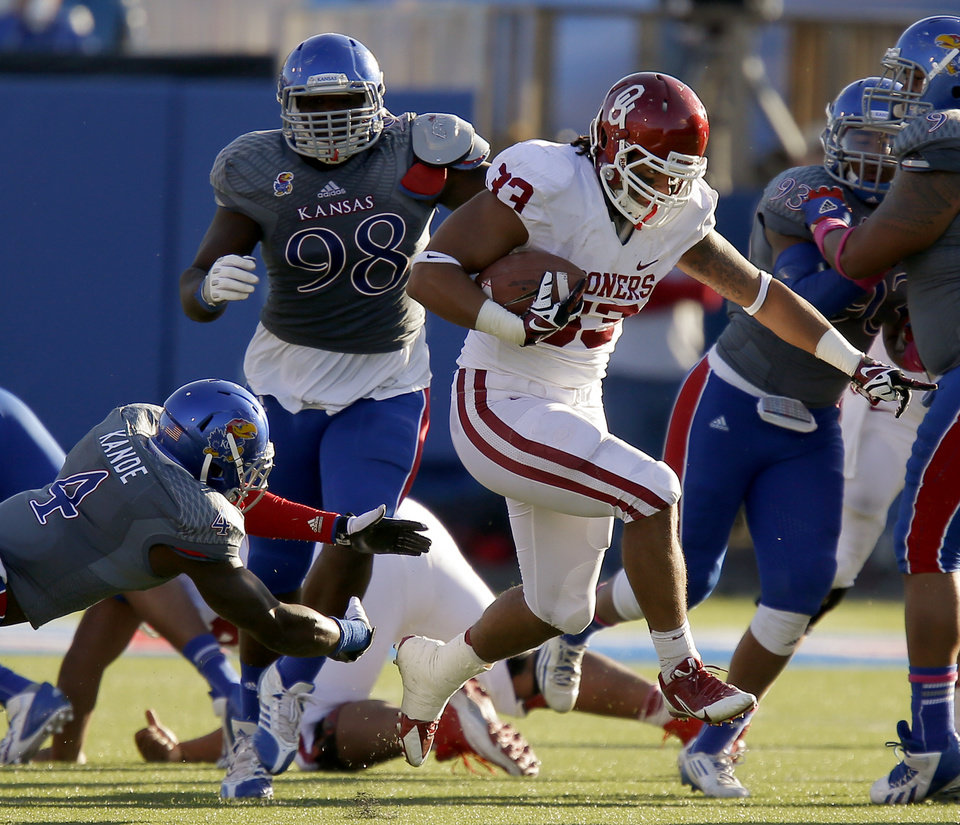Photo - OU's Trey Millard (33) leaps past KU's Prinz Kande (4) and Keon Stowers (98) during the college football game between the University of Oklahoma Sooners (OU) and the University of Kansas Jayhawks (KU) at Memorial Stadium in Lawrence, Kan., Saturday, Oct. 19, 2013. Oklahoma won 34-19. Photo by Bryan Terry, The Oklahoman