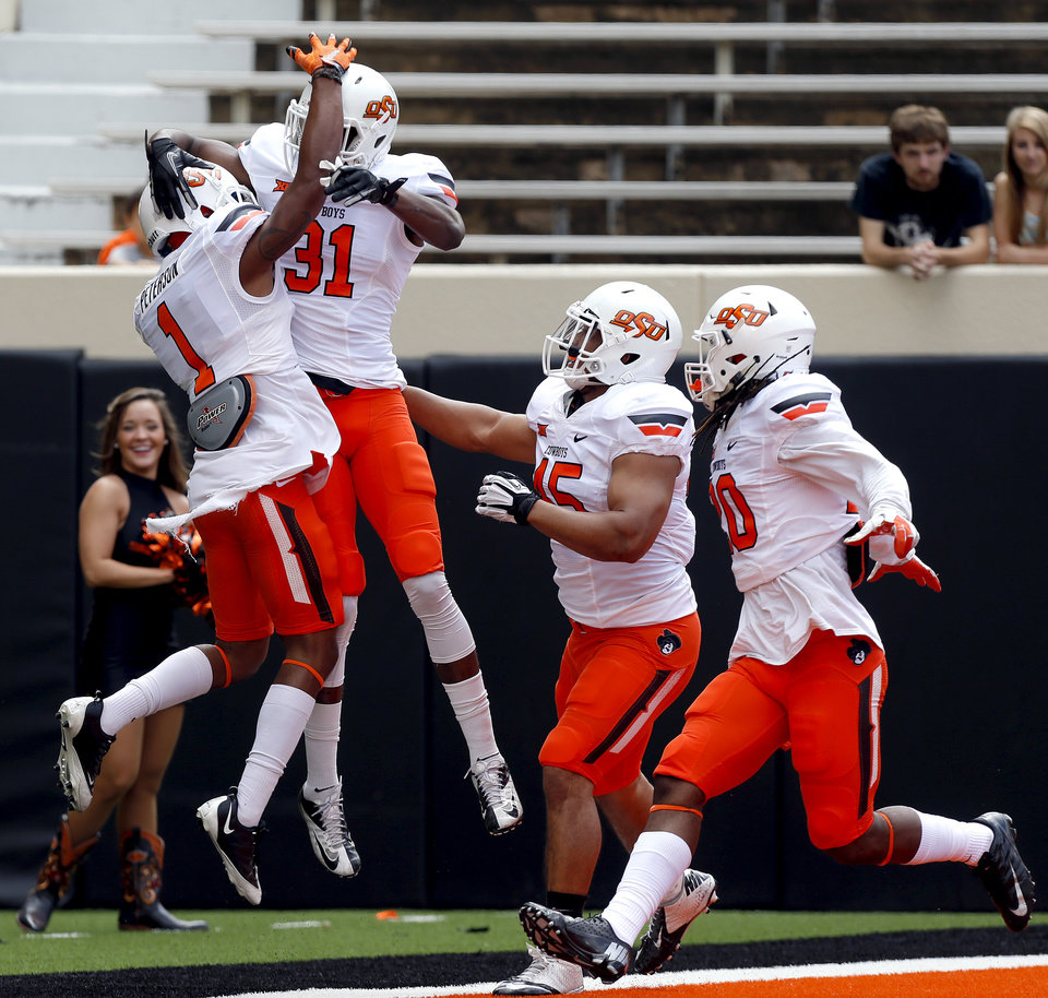 Photo - OSU's Kevin Peterson celebrates an interception and touchdown with Tre Flowers during the Oklahoma State University Spring football game at Boone Pickens Stadium in Stillwater, Okla., Saturday, April, 18, 2015. Photo by Sarah Phipps, The Oklahoman