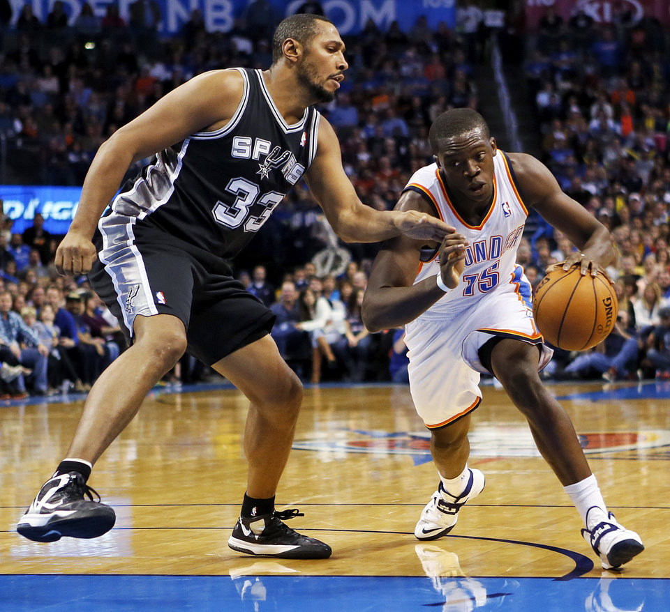 Photo - Oklahoma City's Reggie Jackson (15) drives the ball against San Antonio's Boris Diaw (33) during an NBA basketball game between the Oklahoma City Thunder and the San Antonio Spurs at Chesapeake Energy Arena in Oklahoma City, Wednesday, Nov. 27, 2013. Oklahoma City won, 94-88. Photo by Nate Billings, The Oklahoman