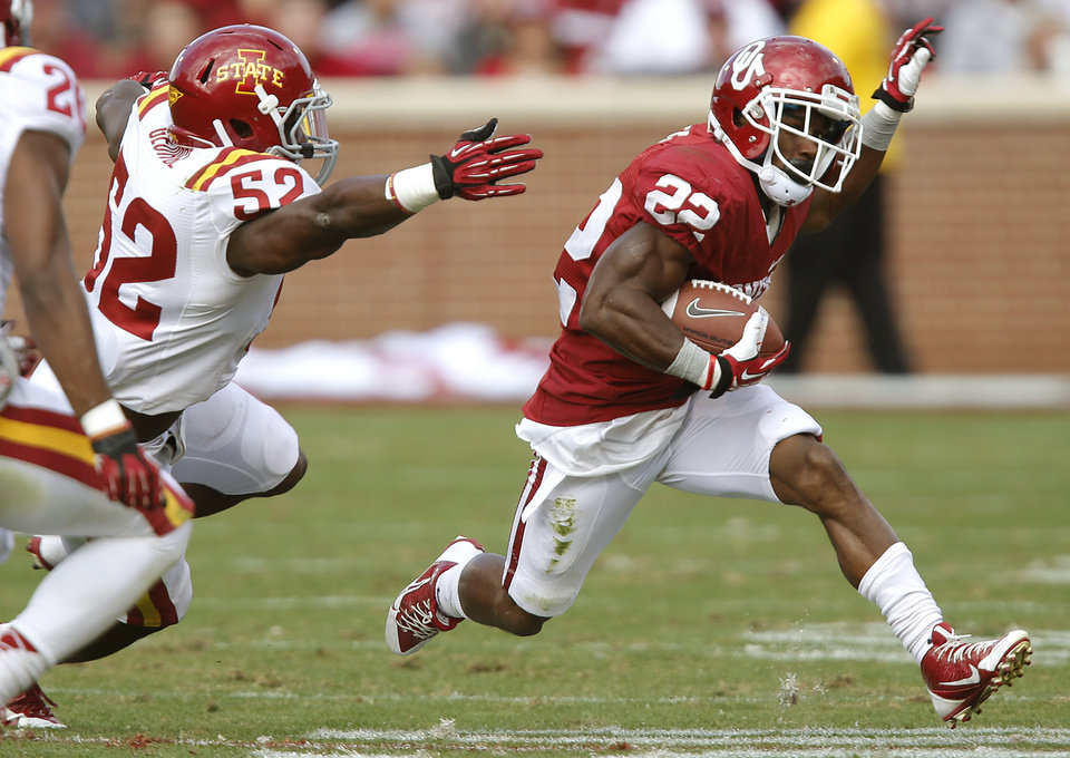 Oklahoma's Roy Finch (22) runs past Iowa State's Jeremiah George (52) during the college football game between the University of Oklahoma Sooners (OU) and the Iowa State University Cyclones (ISU) at Gaylord Family-Oklahoma Memorial Stadium in Norman, Okla. on Saturday, Nov. 16, 2013. Photo by Chris Landsberger, The Oklahoman