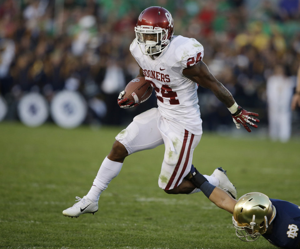 Photo - Oklahoma's Brennan Clay (24) runs out of the tackle of Notre Dame's Austin Collinsworth (28) during the second half of an NCAA college football game on Saturday, Sept. 28, 2013, in South Bend, Ind. Oklahoma defeated Notre Dame 35-21. (AP Photo/Darron Cummings)  ORG XMIT: INDC115