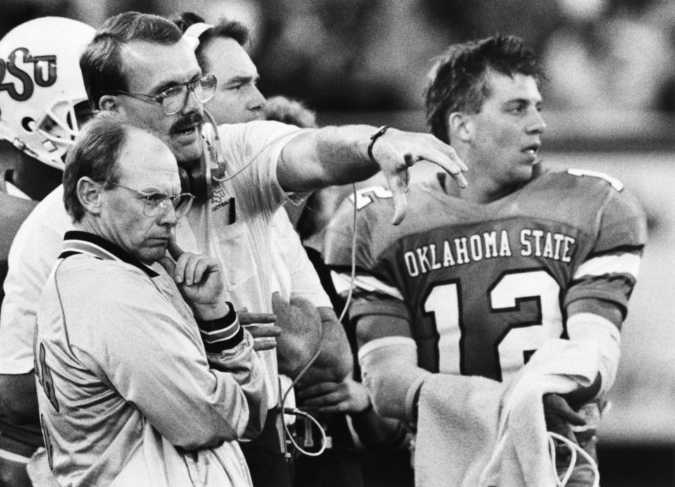 "Photo - ""OSU head coach Pat Jones, left, talks with an assistant coach as quarterback Mike Gundy looks on Saturday"" during the Oklahoma State-Texas A&M game in Stillwater.  The Cowboys won handily, 52-15.