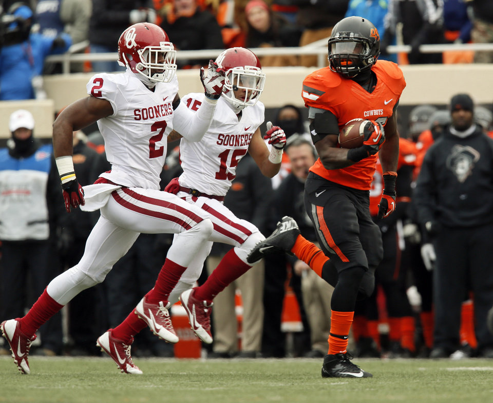Oklahoma State's Desmond Roland (26) breaks away on a long run in front of Oklahoma's Julian Wilson (2) and Zack Sanchez (15) during the Bedlam college football game between the Oklahoma State University Cowboys (OSU) and the University of Oklahoma Sooners (OU) at Boone Pickens Stadium in Stillwater, Okla., Saturday, Dec. 7, 2013. Photo by Nate Billings, The Oklahoman