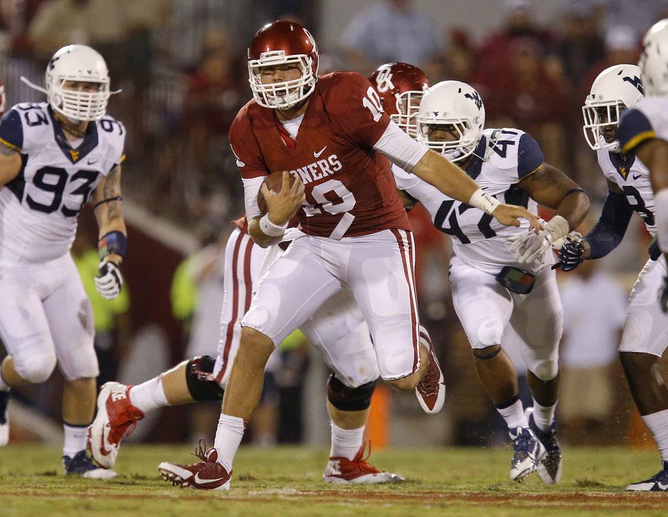 Photo - Oklahoma's Blake Bell (10) runs on his first play during a college football game between the University of Oklahoma Sooners (OU) and the West Virginia University Mountaineers at Gaylord Family-Oklahoma Memorial Stadium in Norman, Okla., on Saturday, Sept. 7, 2013. Photo by Bryan Terry, The Oklahoman