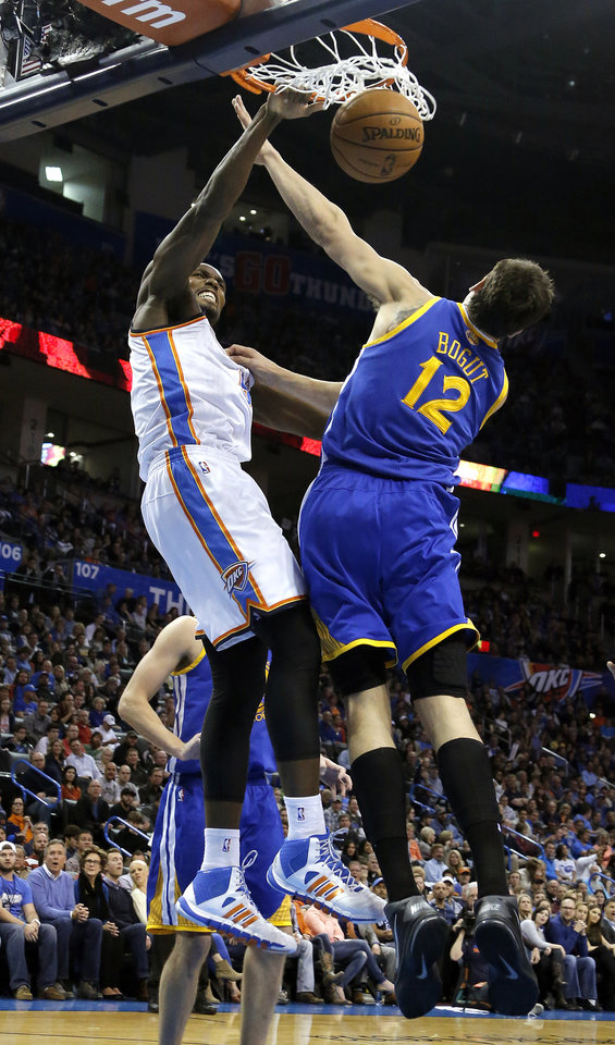 Oklahoma City's Serge Ibaka (9) dunks over Golden State's Andrew Bogut (12) during the NBA game between the Oklahoma City Thunder and the Golden State Warriors at the Chesapeake Energy Arena, Friday, Nov. 29, 2013. Photo by Sarah Phipps, The Oklahoman