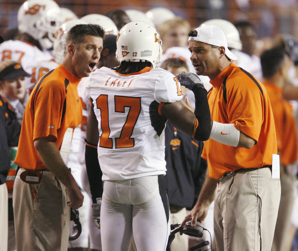 Photo - COLLEGE FOOTBALL: Oklahoma State University (OSU) head coach Mike Gundy and associate head coach Joe Deforest talk with cornerback Jacob Lacey after a Texas score as the Cowboys play the University of Texas Longhorns at Darrell K. Royal-Texas Memorial Stadium in Austin, TX on Saturday, November 4, 2006. by Steve Sisney, The Oklahoman  ORG XMIT: KOD