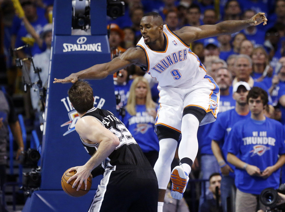 Photo - Oklahoma City Thunder forward Serge Ibaka (9) gets up to block a shot by San Antonio Spurs center Tiago Splitter (22) in the second quarter of Game 4 of the Western Conference finals NBA basketball playoff series in Oklahoma City, Tuesday, May 27, 2014. (AP Photo/Sue Ogrocki)