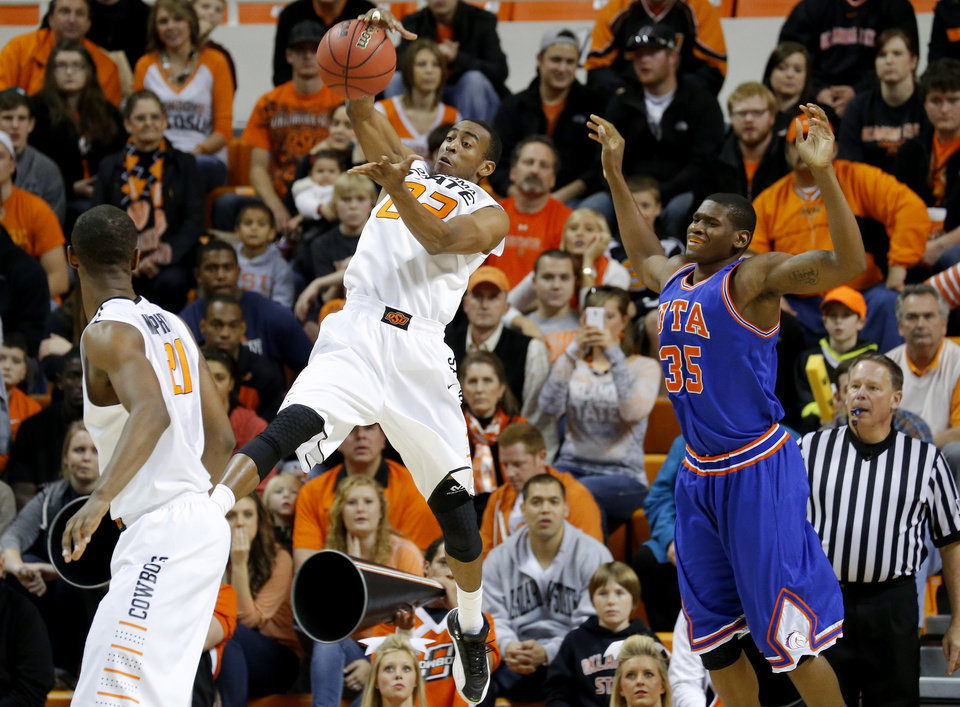 Photo - Oklahoma State's Markel Brown (22) steals the ball in front of Texas-Arlington's Brandon Edwards (35) during a college basketball game between Oklahoma State University and UT Arlington at Gallagher-Iba Arena in Stillwater, Okla., Wednesday, Dec. 19, 2012. Photo by Bryan Terry, The Oklahoman