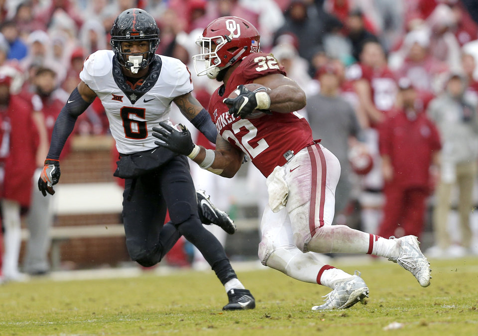 Photo - Oklahoma's Samaje Perine (32) rushes as Oklahoma State's Ashton Lampkin (6) defends during the Bedlam college football game between the Oklahoma Sooners (OU) and the Oklahoma State Cowboys (OSU) at Gaylord Family - Oklahoma Memorial Stadium in Norman, Okla., Saturday, Dec. 3, 2016. OU won 38-20. Photo by Sarah Phipps, The Oklahoman