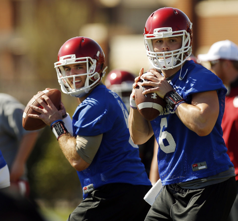 Photo -                    OU quarterbacks Trevor Knight, left, and Baker Mayfield look to pass during a drill at spring football practice on March 23.                     Photo by Nate Billings, The Oklahoman
