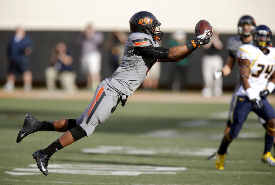Photo - Oklahoma State's Josh Stewart (5) catches pass during a college football game between Oklahoma State University (OSU) and West Virginia University at Boone Pickens Stadium in Stillwater, Okla., Saturday, Nov. 10, 2012. Photo by Bryan Terry, The Oklahoman