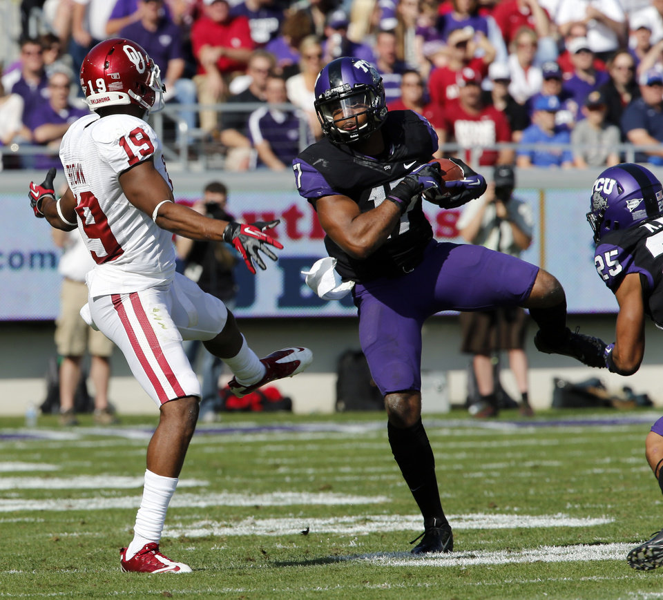 Photo - TCU's Sam Carter (17) intercepts a Landry Jones pass intended for Justin Brown (19) during the college football game between the University of Oklahoma Sooners (OU) and the Texas Christian University Horned Frogs (TCU) at Amon G. Carter Stadium in Fort Worth, Texas, on Saturday, Dec. 1, 2012. Photo by Steve Sisney, The Oklahoman
