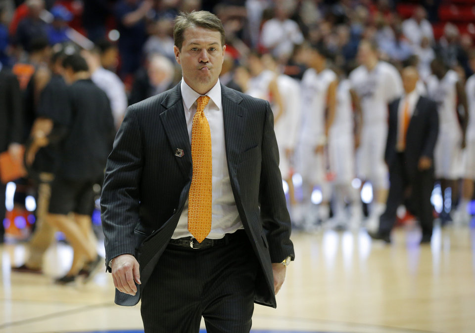 Photo - OSU coach Travis Ford walks off the court after losing in the second round game of the NCAA men's college basketball tournament at Viejas Arena in San Diego, between Oklahoma State and Gonzaga Friday, March 21, 2014. Gonzaga won 85-77. Photo by Bryan Terry, The Oklahoman