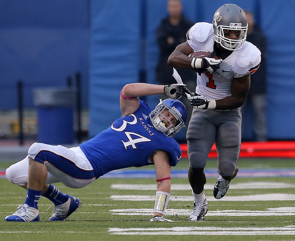 Oklahoma State\'s Joseph Randle (1) gets by Kansas \'s Huldon Tharp (34) during the college football game between Oklahoma State University (OSU) and the University of Kansas (KU) at Memorial Stadium in Lawrence, Kan., Saturday, Oct. 13, 2012. Photo by Sarah Phipps, The Oklahoman