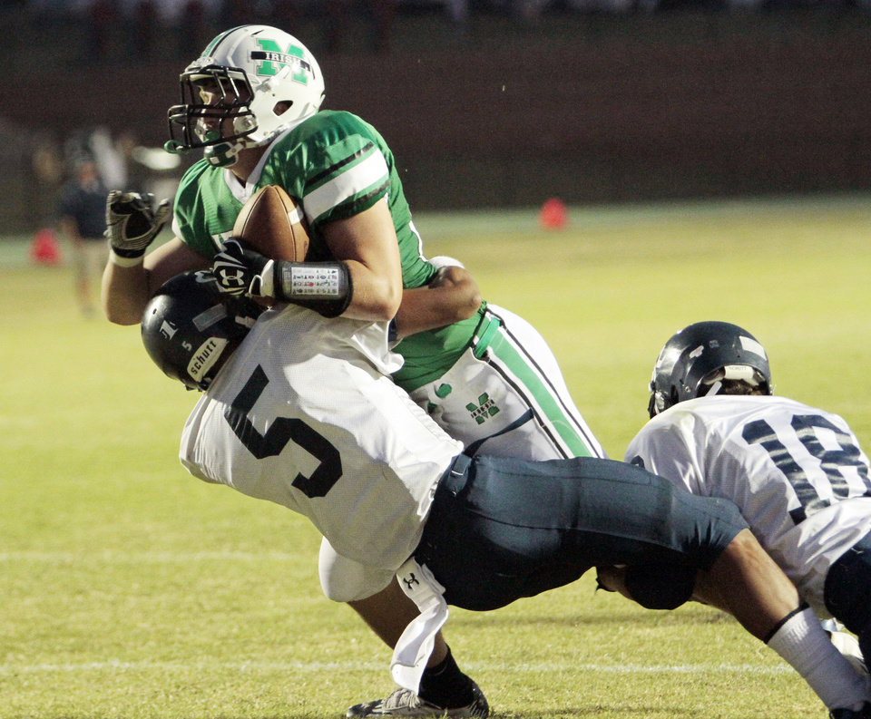 Photo - McGuinness' David Love is brought down after a catch by Justin Brown (5) and Seth Jones (18) as El Reno Indians play the Bishop McGuinness Fighting Irish in high school football on Friday, Sept. 21, 2012 in Oklahoma City, Okla.  Photo by Steve Sisney, The Oklahoman