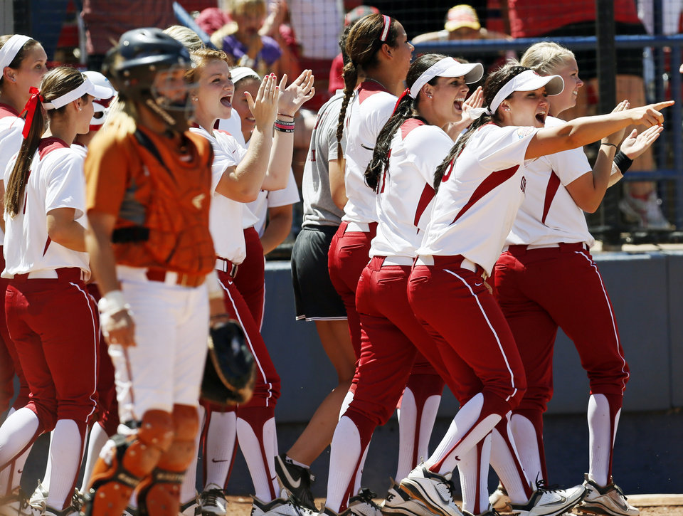 Photo - OU players near Texas catcher Mandy Ogle (5) point to Keilani Ricketts (10) at second base after she doubled to score Georgia Casey (42) in the third inning during an NCAA softball game in the Women's College World Series between Oklahoma and Texas at ASA Hall of Fame Stadium in Oklahoma City, Saturday, June 1, 2013. Oklahoma won 10-2 in five innings. Photo by Nate Billings, The Oklahoman