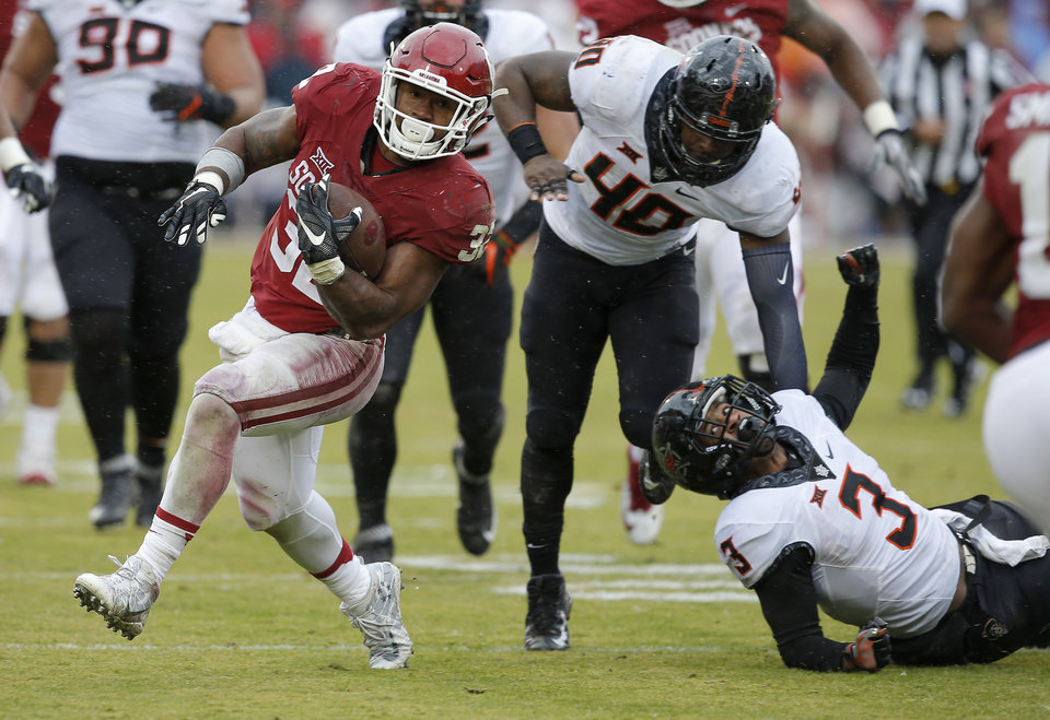 Photo - Oklahoma's Samaje Perine (32) runs past Oklahoma State's Devante Averette (40) and Kenneth Edison-McGruder (3) during the Bedlam college football game between the Oklahoma Sooners (OU) and the Oklahoma State Cowboys (OSU) at Gaylord Family - Oklahoma Memorial Stadium in Norman, Okla., Saturday, Dec. 3, 2016. Oklahoma won 38-20. Photo by Bryan Terry, The Oklahoman