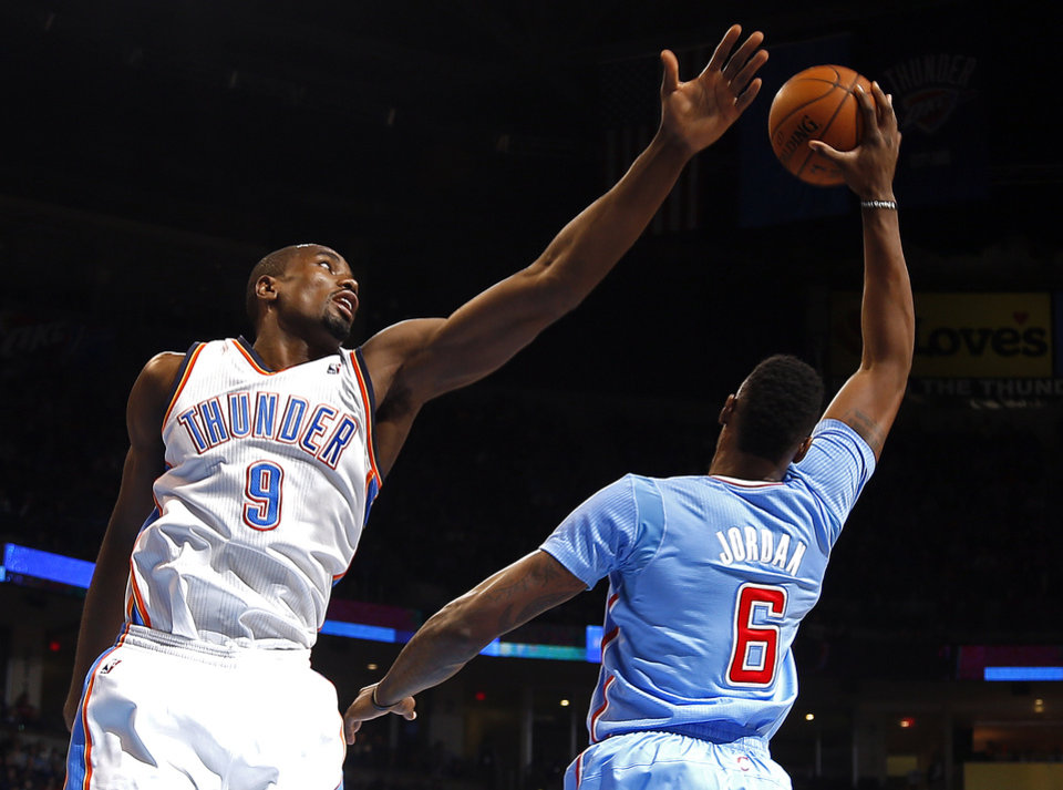 Photo - Los Angeles' DeAndre Jordan (6) grabs a rebound from Oklahoma City 's Serge Ibaka (9) during the NBA game between the Oklahoma City Thunder and the Los  Angeles Clippers at the Chesapeake Energy Arena, Sunday, Feb. 23, 2014. Photo by Sarah Phipps, The Oklahoman