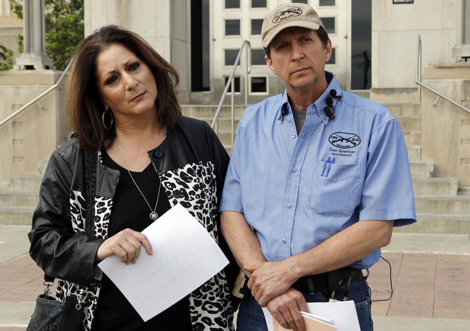 Photo - Don Spencer, vice president of the Oklahoma Second Amendment Association and Lana Cohlmia, attorney speak to the media outside the Cleveland County Courthouse on Wednesday, April 15, 2015 in Norman, Okla.  Photo by Steve Sisney, The Oklahoman