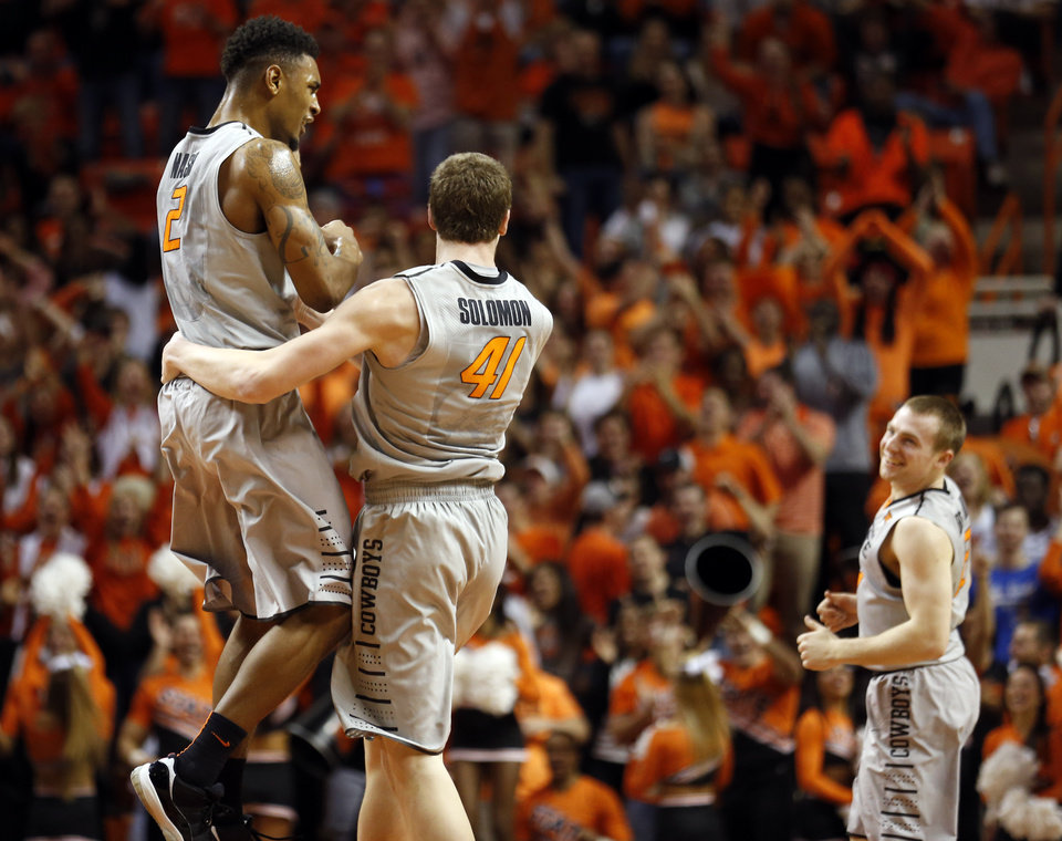 Photo - Oklahoma State's Le'Bryan Nash (2), Mitchell Solomon (41) and Phil Forte III (13) celebrate a Solomon dunk during the men's college basketball game between Oklahoma State University and the University of Kansas at Gallagher-Iba Arena in Stillwater, Okla.,  Saturday, Feb. 7, 2015. Photo by Sarah Phipps, The Oklahoman