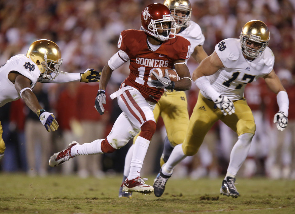 Photo - OU's Jalen Saunders (18) runs past Notre Dame's KeiVarae Russell (6), left, and Zeke Motta (17) during the college football game between the University of Oklahoma Sooners (OU) and the Notre Dame Fighting Irish at Gaylord Family-Oklahoma Memorial Stadium in Norman, Okla., Saturday, Oct. 27, 2012. Oklahoma lost 30-13. Photo by Bryan Terry, The Oklahoman
