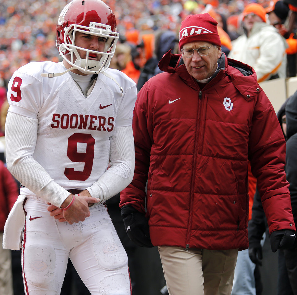 Oklahoma's Trevor Knight (9) walks off the field holding his wrist with a trainer during the Bedlam college football game between the Oklahoma State University Cowboys (OSU) and the University of Oklahoma Sooners (OU) at Boone Pickens Stadium in Stillwater, Okla., Saturday, Dec. 7, 2013. Photo by Chris Landsberger, The Oklahoman