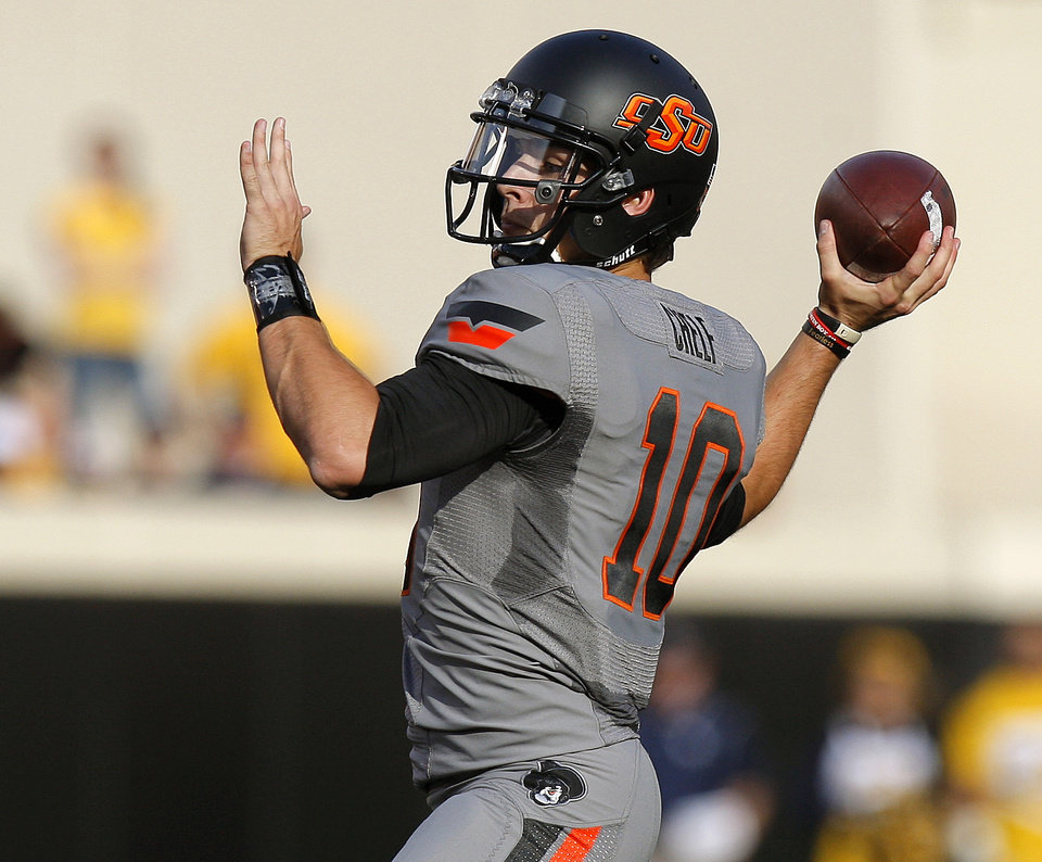 Oklahoma State\'s Clint Chelf (10) throws a touchdown pass during a college football game between Oklahoma State University (OSU) and the University of West Virginia at Boone Pickens Stadium in Stillwater, Okla., Saturday, Nov. 10, 2012. Photo by Bryan Terry, The Oklahoman