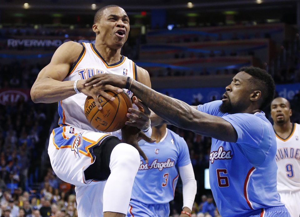 Los Angeles Clippers center DeAndre Jordan (6) attempts to take the ball away as Oklahoma City Thunder guard Russell Westbrook (0) drives in the fourth quarter of an NBA basketball game in Oklahoma City, Sunday, Feb. 23, 2014. Los Angeles won 125-117. (AP Photo/Sue Ogrocki)