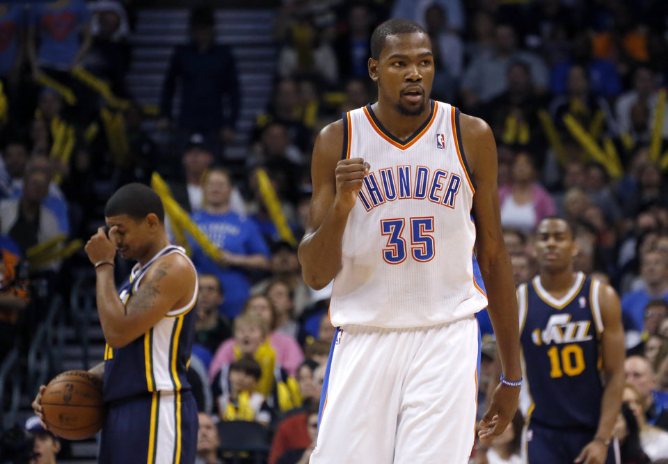 Photo - Oklahoma City's Kevin Durant (35) celebrates in front of Utah's Earl Watson and Alec Burks (10) during the NBA game between the Oklahoma City and the Utah Jazz and the Chesapeake Energy Arena, Friday,Nov. 30, 2012. Photo by Sarah Phipps, The Oklahoman