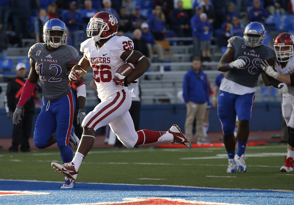 OU's Damien Williams (26) scores a touchdown in the fourth quarter beside KU's Dexter McDonald (12) and Keon Stowers (98) during the college football game between the University of Oklahoma Sooners (OU) and the University of Kansas Jayhawks (KU) at Memorial Stadium in Lawrence, Kan., Saturday, Oct. 19, 2013. Oklahoma won 34-19. Photo by Bryan Terry, The Oklahoman