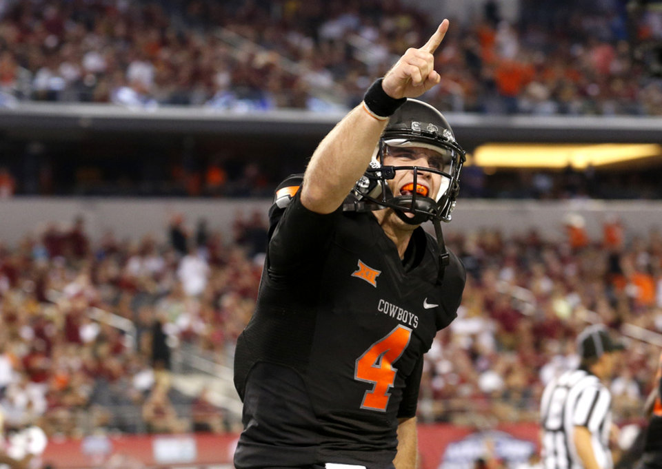 Photo - Oklahoma State's J.W. Walsh (4) celebrates a touchdown in the 3rd quarter of the college football game between Oklahoma State University (OSU) and Florida State University (FSU) at the AdvoCare Cowboys Classic at At&T Stadium in Arlington, Texas,  Saturday, Aug. 30, 2014. Photo by Sarah Phipps, The Oklahoman