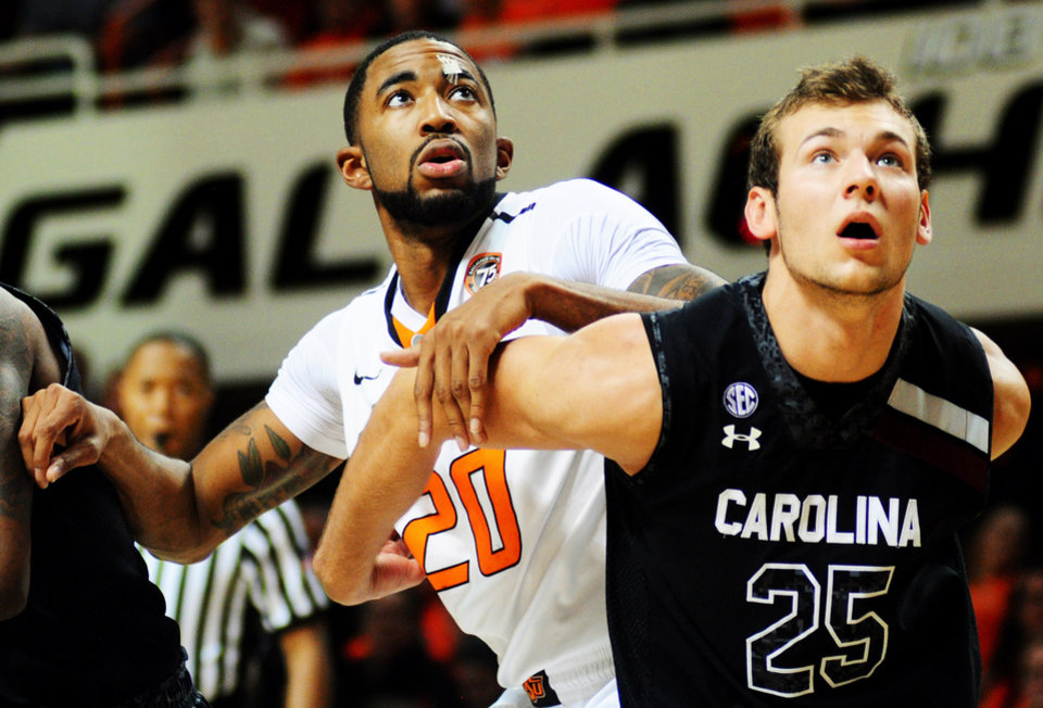 Oklahoma State forward Michael Cobbins fights for position with South Carolina defender Mindaugas Kacinas during a game against South Carolina at Gallagher-Iba Arena in Stillwater on Dec. 6, 2013. The Cowboys defeated South Carolina 79-52, lead by 16 points from forward Le\'bryan Nash. Photo by KT King/For the Tulsa World