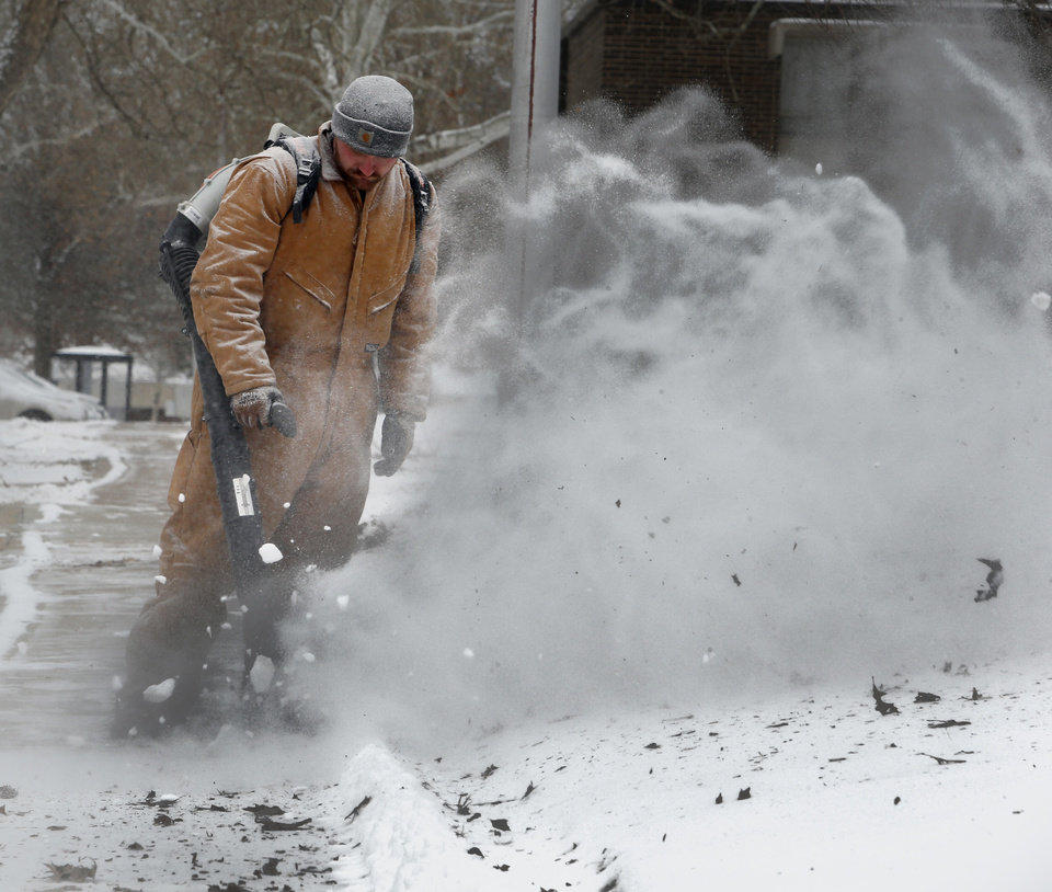 Photo - Eric Davis, irrigation department, uses a backpack blower to remove snow from sidewalks in frigid weather on the campus of the University of Oklahoma (OU) on Thursday, Feb. 6, 2014 in Norman, Okla.  Photo by Steve Sisney, The Oklahoman
