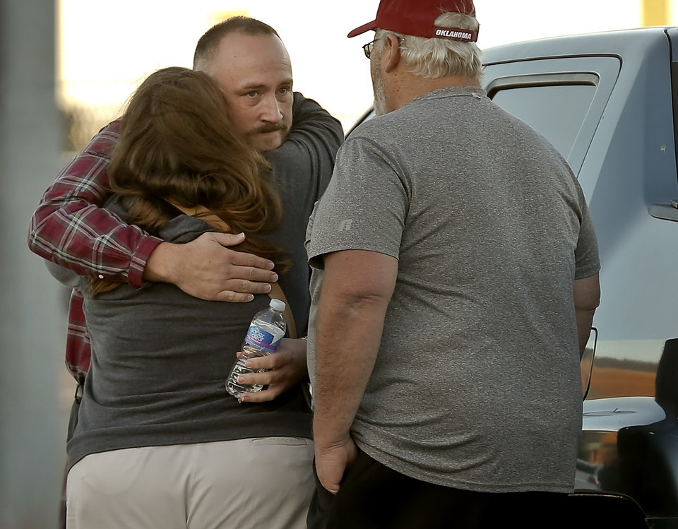 Photo - One of the released hostages, middle, hugs family members after authorities cleared the scene of a hostage situation at Nextep in Norman Monday, Nov. 10, 2014.  in Norman, Okla. on Monday, Nov. 10, 2014.  Photo by Chris Landsberger, The Oklahoman