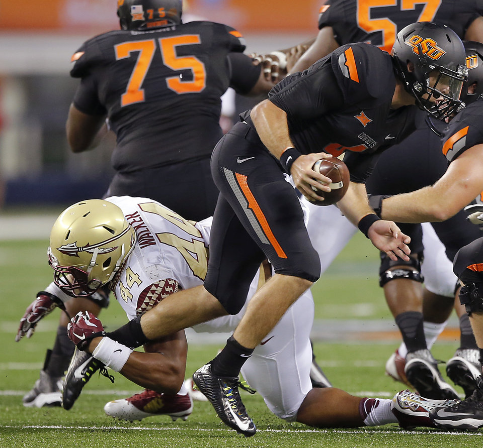 Photo - Oklahoma State's J.W. Walsh (4) breaks away from Florida State's DeMarcus Walker (44) during the college football game between Oklahoma State University (OSU) and Florida State University (FSU) at the AdvoCare Cowboys Classic at AT&T Stadium in Arlington, Texas on Saturday, Aug. 30, 2014. Photo by Chris Landsberger, The Oklahoman
