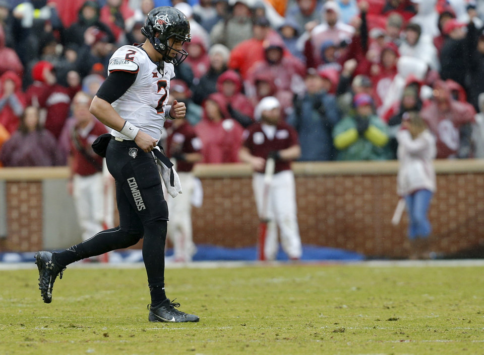 Photo - Oklahoma State's Mason Rudolph (2) walks off the field after being sacked in the fourth quarter during the Bedlam college football game between the Oklahoma Sooners (OU) and the Oklahoma State Cowboys (OSU) at Gaylord Family - Oklahoma Memorial Stadium in Norman, Okla., Saturday, Dec. 3, 2016. OU won 38-20. Photo by Sarah Phipps, The Oklahoman