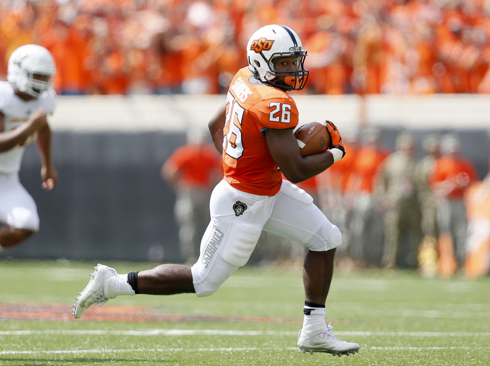 Photo - Oklahoma State running back Barry J Sanders returns a punt on Saturday against Southeastern Louisiana at Boone Pickens Stadium in Stillwater. (Photo by Sarah Phipps, The Oklahoman)