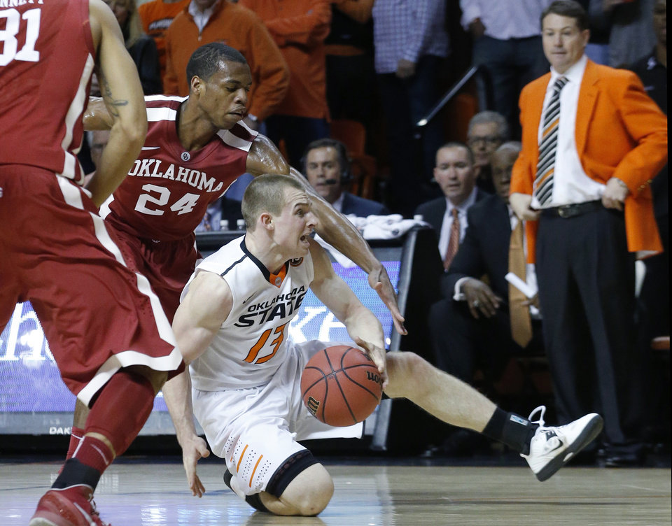 Photo - Oklahoma State guard Phil Forte (13) keeps the ball from Oklahoma guard Buddy Hield (24) in the second half of an NCAA college basketball game in Stillwater, Okla., Saturday, Feb. 15, 2014. Oklahoma won 77-74. (AP Photo/Sue Ogrocki)