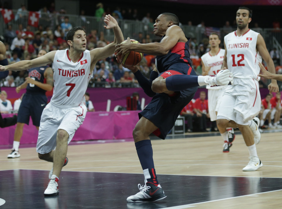 USA's Russell Westbrook, center, drives to the basket against Tunisia's Mourad El Mabrouk, left, during a men's basketball game at the 2012 Summer Olympics, Tuesday, July 31, 2012, in London. (AP Photo/Charles Krupa) ORG XMIT: OBKO171