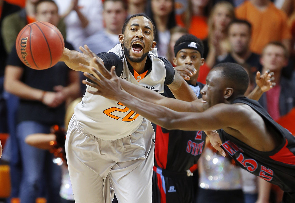 Photo - Oklahoma State's Michael Cobbins reaches for the ball beside Delaware State's Ashwell Boyd (45) during an NCAA college basketball between Oklahoma State University and Delaware State at Gallagher-Iba Arena in Stillwater, Okla., Tuesday, December 17, 2013. Photo by Bryan Terry, The Oklahoman